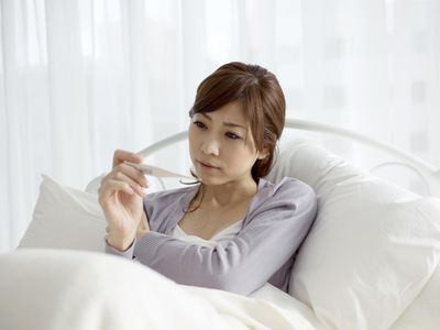 A woman in bed looking at a thermometer, wondering if your BBT chart can tell her if she is pregnant