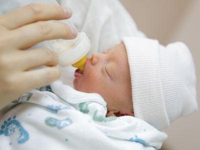Mother bottle feeding her preemie