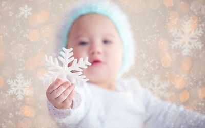 baby holding a snowflake