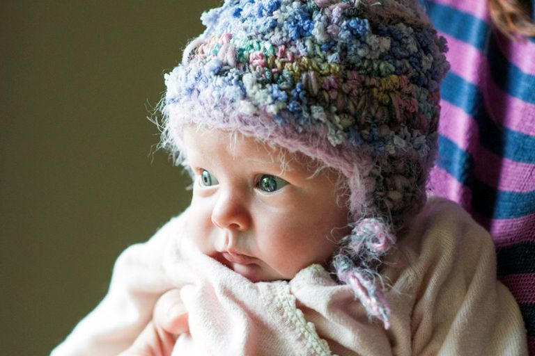 A newborn infant girl (age 3 weeks) wearing a homemade knitted hat, while being held by her mother.