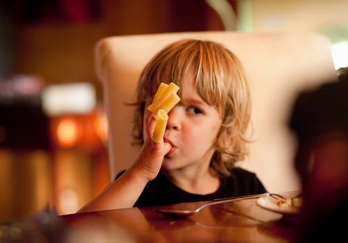 Bad table manners - boy eating pasta on fingers