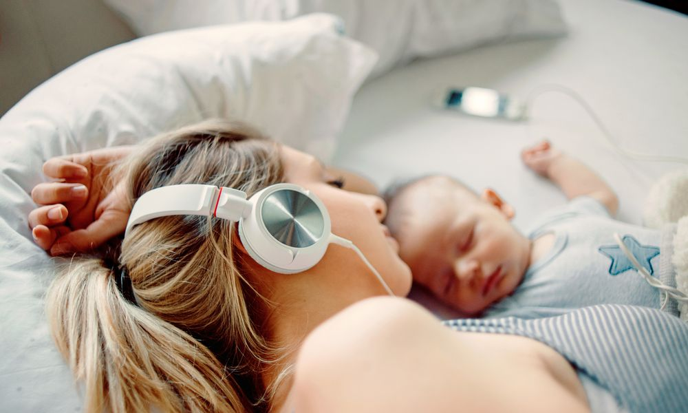 New mom listening to music and napping with her baby