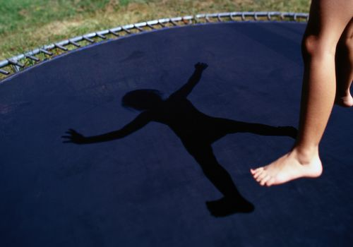child's legs jumping on a trampoline