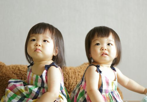 Twin girls in identical dresses sitting on a couch