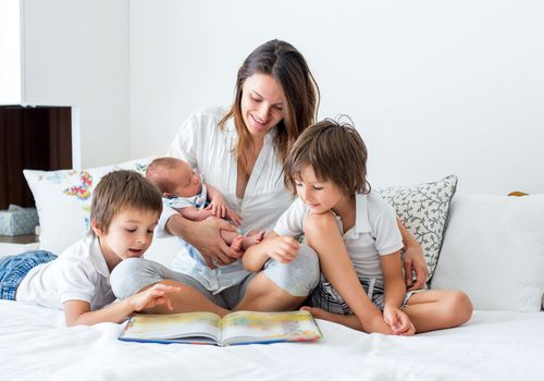 Mom reading to newborn and older kids