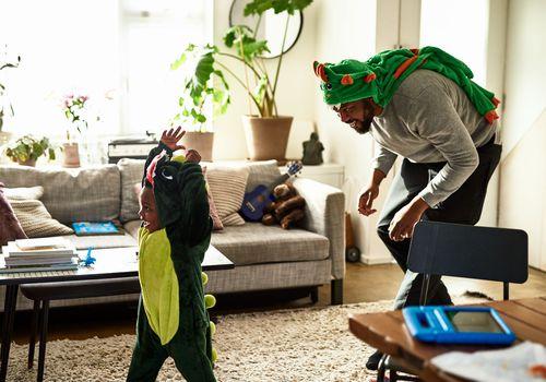 BIPOC man playing with his kid.