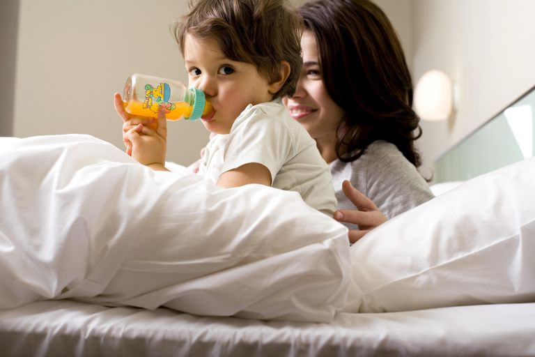 Mother and child drinking juice in bed