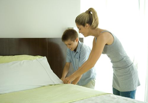 Boy helping mother make bed