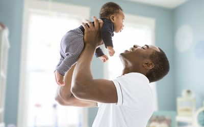 Black father lifting baby son