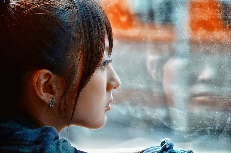 woman looking out window, bad periods preventing her from living her life
