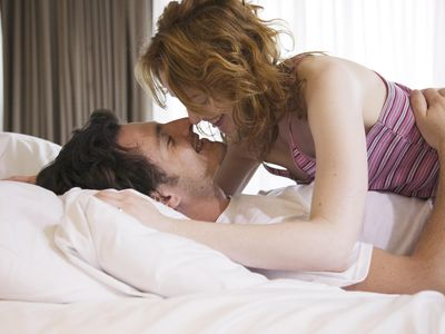 Young couple kissing in bed, smiling, side view, close-up