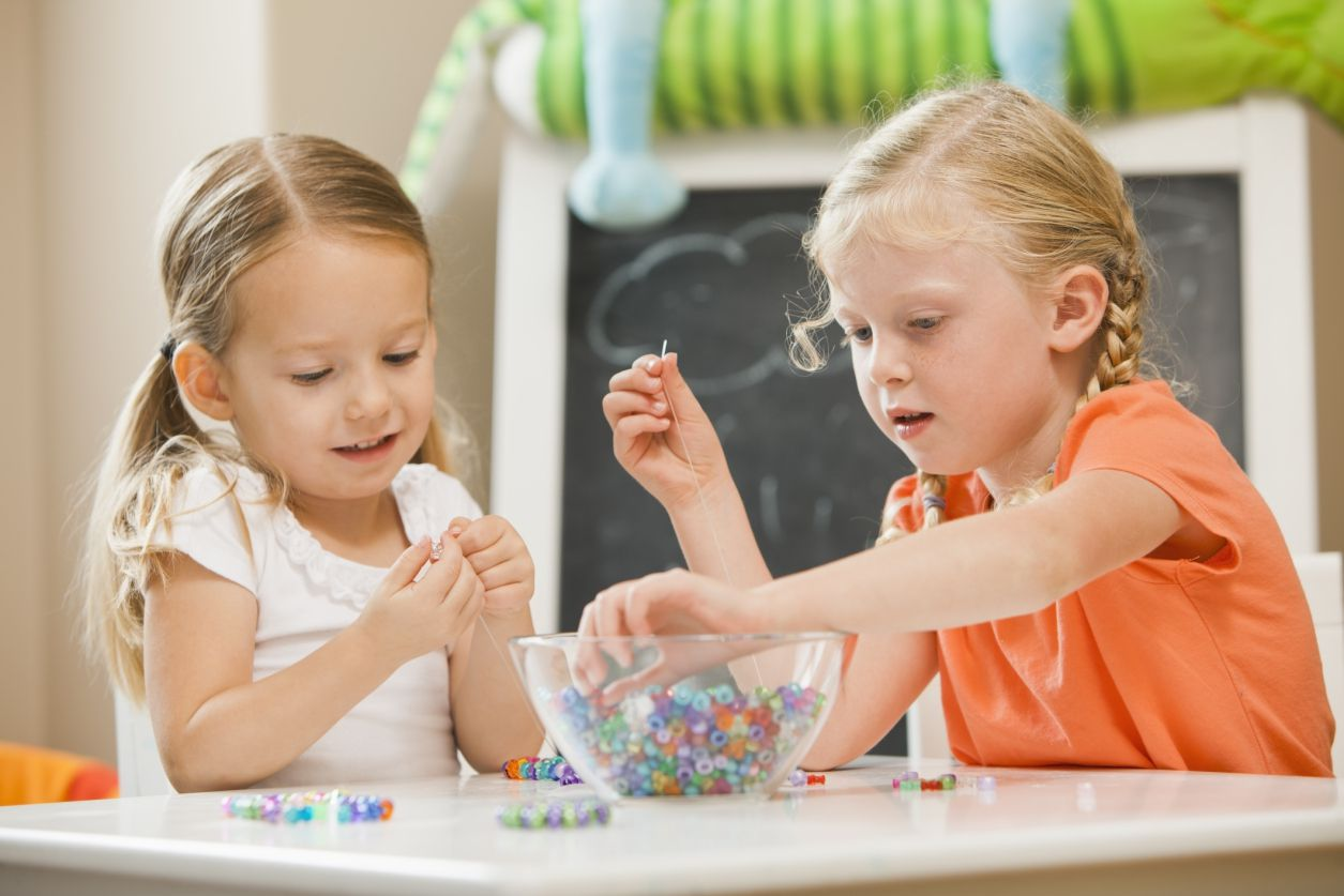 two young girls stringing beads