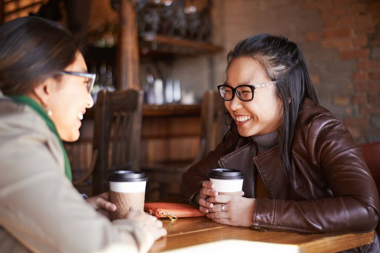 Sharing coffee and a few giggles as a woman supports a friend with infertility