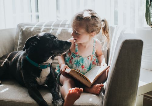 little girl reading a book with a dog