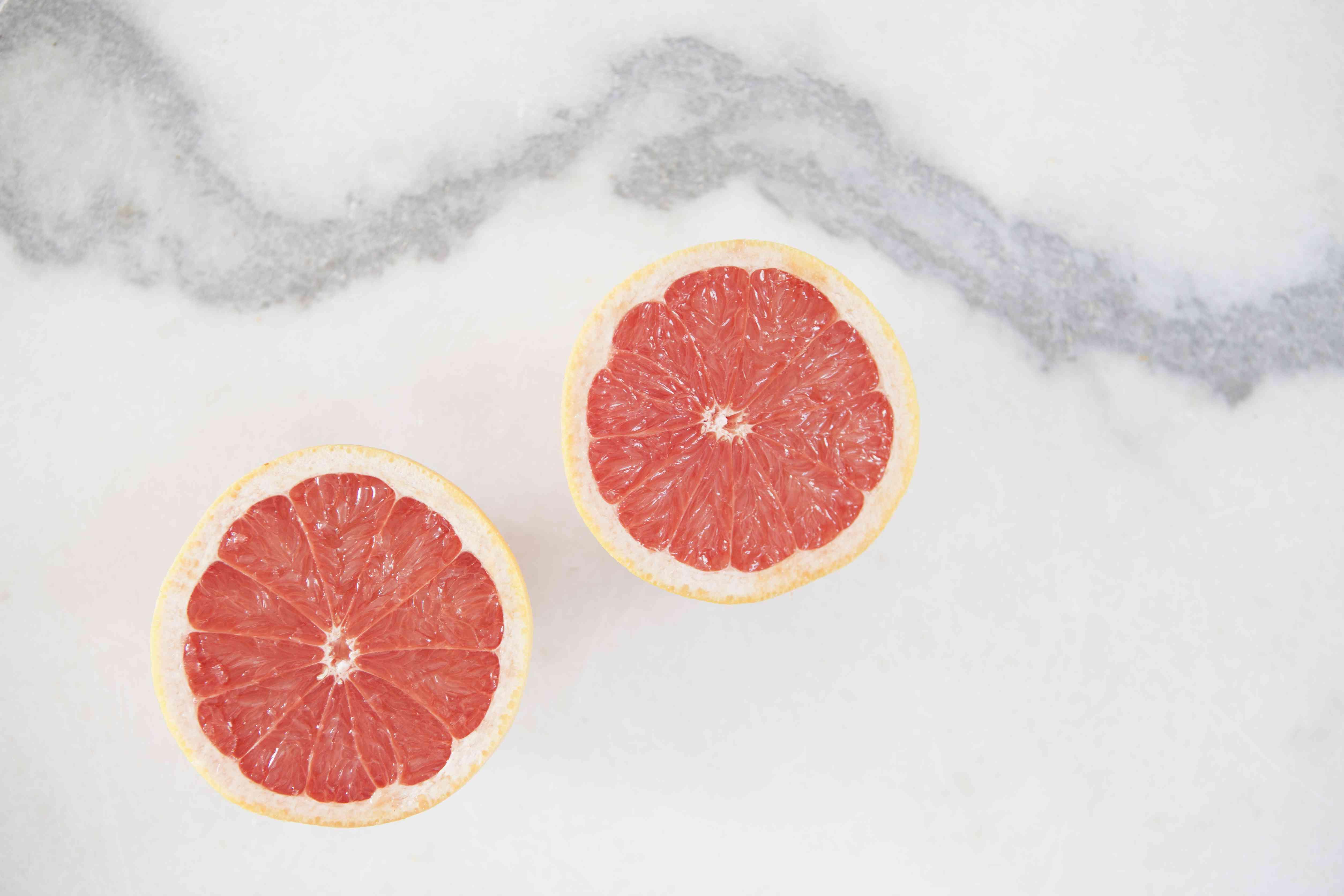 Directly above shot of sliced grapefruit on white background
