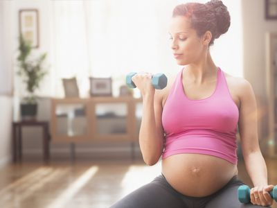 Pregnant mixed race woman exercising with dumbbells
