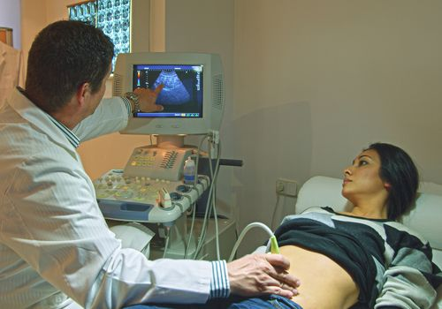 Doctor using ultrasound on pregnant woman