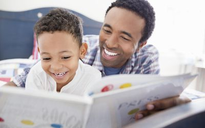 Verbally gifted boy reading with his father