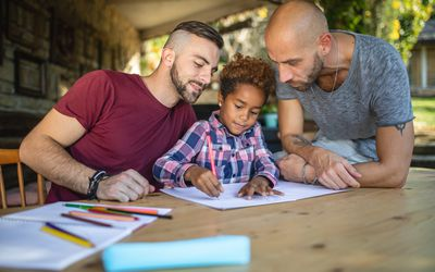 two dads helping kid do homework