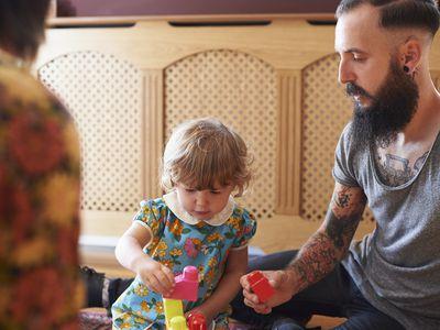tattooed man helping toddler girl play with blocks