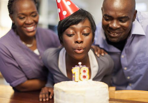 African female teenager blowing out the candles on her 18th birthday cake, surrounded by family