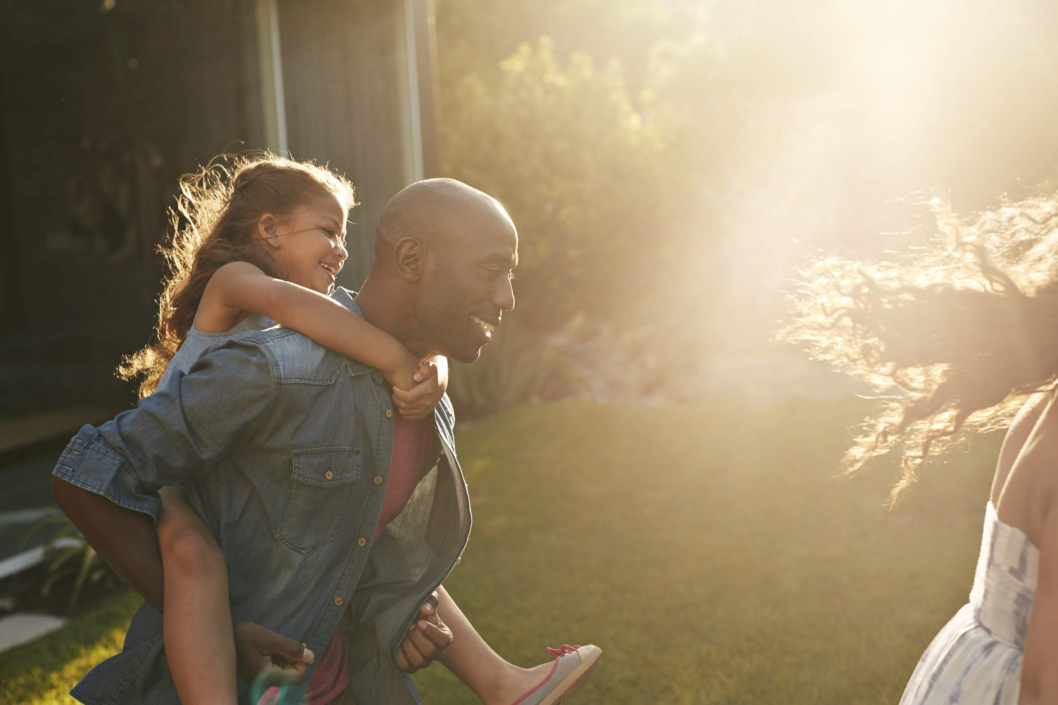 Father giving piggyback ride to daughter outdoors