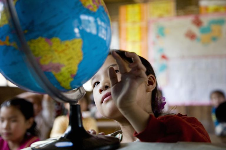 China, Guangxi Province, girl (6-9) looking at globe in class