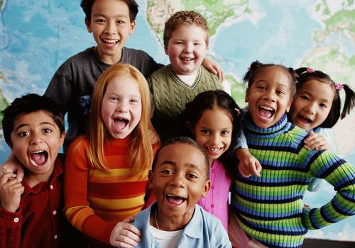 Kids of different races smiling in a classroom