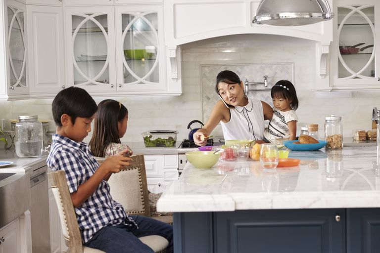 Busy mom in the kitchen with three children