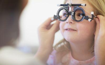 Eye doctor examining young girl's vision