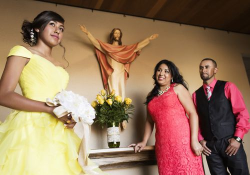 Hispanic family celebrating quinceanera in church