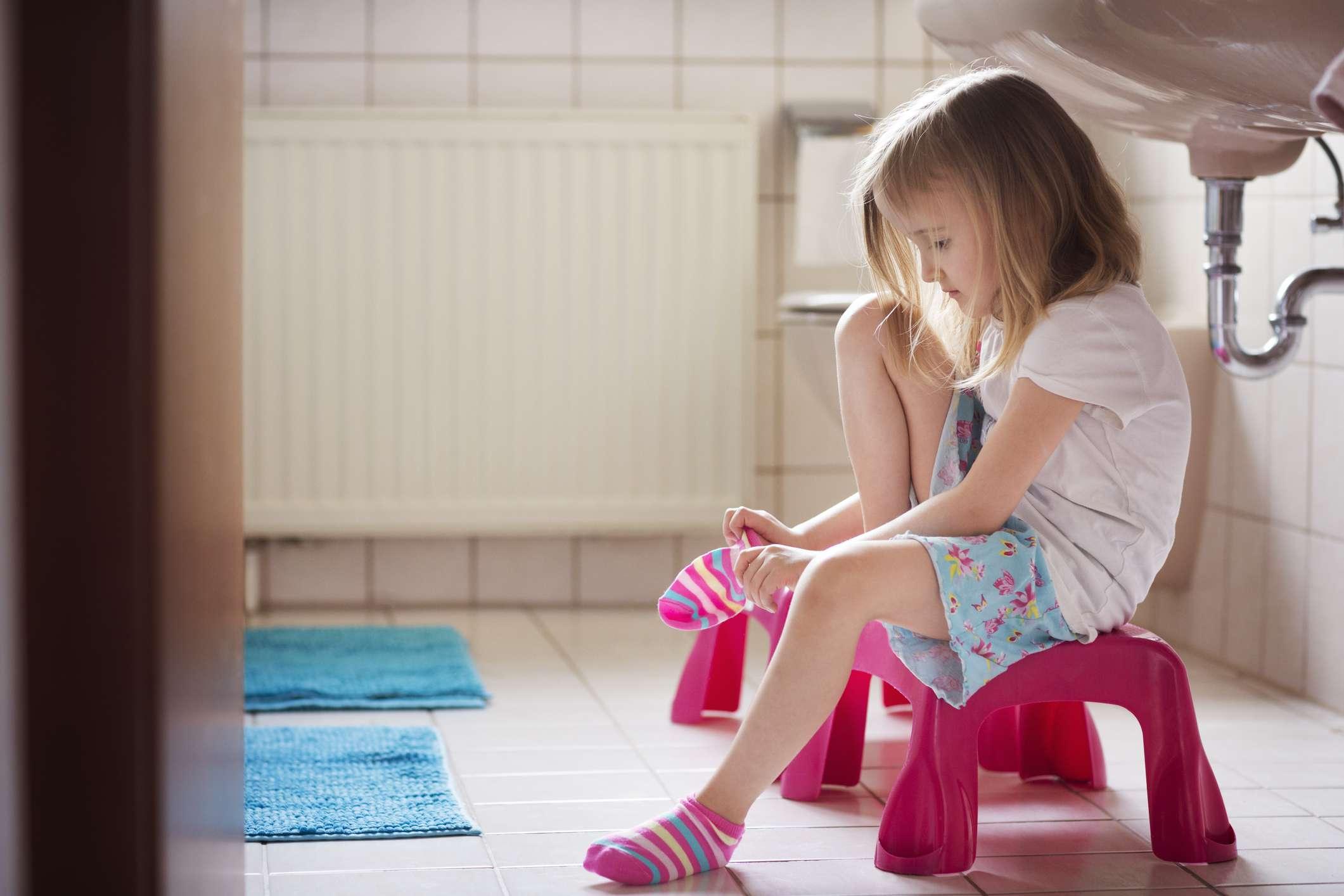 Girl (4-5) putting socks on independently