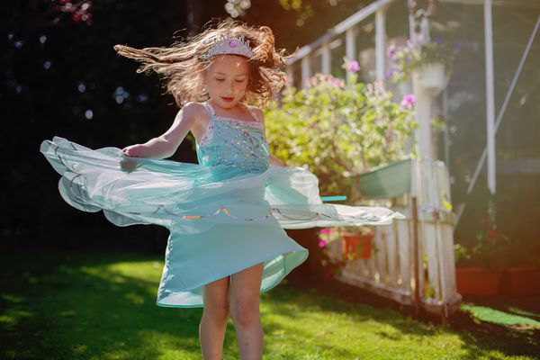 Girl wearing a princess dress dancing in a field