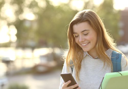 Female college student smiling and texting