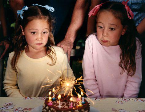 Twins celebrating birthday with cake