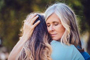 Grandmother lovingly embracing and holding teenage granddaughter