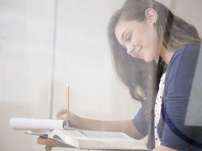 teenage girl writing at desk