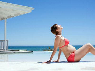 Pregnant woman sunbathing next to pool