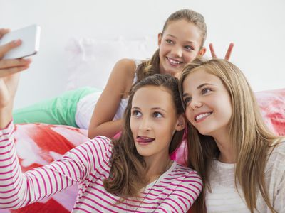 Three tween girls taking a picture of themselves with a mobile phone at a slumber party