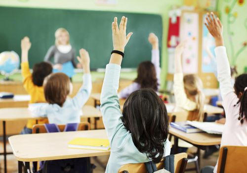 Children are raised hands in classroom.