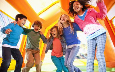 Five smiling kids jumping in a bouncy house