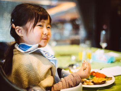 Toddler girl having meal in a restaurant