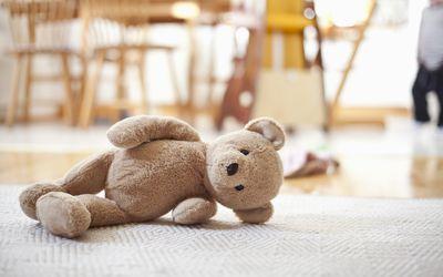 Abandoned teddy bear lying on carpet in house
