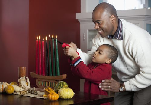 Dad and son lighting Kinara for Kwanzaa.