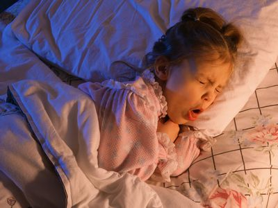 young girl coughing in bed