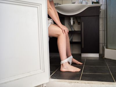 Woman sitting on toilet at home