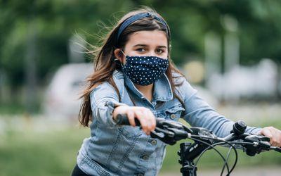 Girl on a bike wearing a mask