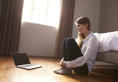 Young woman sitting alone in room with laptop in front of her