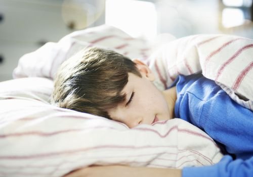 Young boy asleep in a sunlit room
