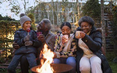 grandparents and grandchildren drinking hot cocoa at campfire